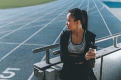 Sportswoman with sport bottle on running track on stadium Royalty Free Stock Photo