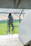 Sportswoman with sport bottle standing at handrail on stadium. Young sportswoman with sport bottle standing at handrail on stadium Royalty Free Stock Photo