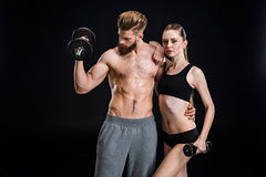 Sportswoman and sportsman training with dumbbells isolated on black. In studio Royalty Free Stock Photo