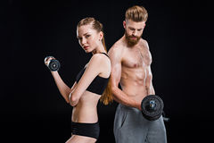 Sportswoman and sportsman training with dumbbells isolated on black. In studio Stock Photo