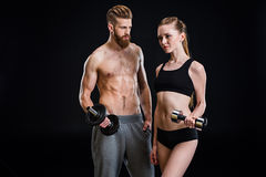 Sportswoman and sportsman training with dumbbells isolated on black. In studio Royalty Free Stock Photos