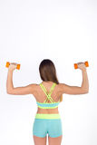 Sportswoman in sportswear exercises with dumbbells stock images