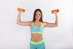 Sportswoman in sportswear exercises with dumbbells stock photo