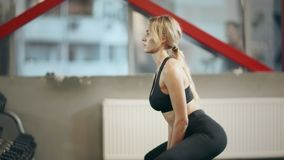 Sportswoman squatting with dumbbells in fitness center. Athlete woman practicing squat with weight in gym. Closeup concentrated woman lifting weights in sport stock video