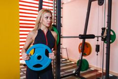 A sportswoman, stands in the gym holding a blue pancake for the bar. A beautiful sportswoman, with light long hair, European appearance, dressed in a black Stock Photography