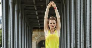 Sportswoman stretching on Pont de Bir-Hakeim bridge in Paris Royalty Free Stock Photos