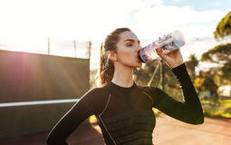 Sportswoman taking break after training session on tennis court. Portrait of beautiful young woman drinking water after workout on a sunny day. Sportswoman Royalty Free Stock Photos
