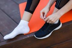 Sportswoman ties shoelaces on sneaker. In gym, sitting on rug on wooden floor Stock Image