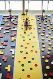 Sportswoman on the top of the wall in rock-climbing center Stock Photo