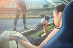 Sportswoman with towel and bottle sitting on stadium seat and looking at sporty girl. Young sportswoman with towel and bottle sitting on stadium seat and looking Stock Image