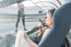 Sportswoman with towel and bottle sitting on stadium seat and looking at sporty girl. Young sportswoman with towel and bottle sitting on stadium seat and looking Royalty Free Stock Photos