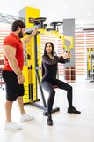 Sportswoman train with coaches help in gym. The coach is engaged with a women in the gym. The concept of a healthy lifestyle stock image