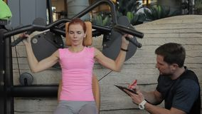 Sportswoman is training arms and her personal male instructor is observing the exercising in the gym. Lady in pink t-shirt is sitting on the equipment and stock footage