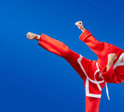 Sportswoman is training kick leg on a blue background Royalty Free Stock Image