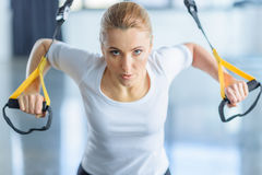 Sportswoman training with resistance band in sports center Stock Photos