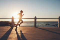 Sportswoman training on seaside promenade at sunset Stock Images