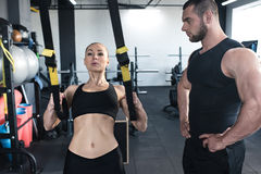 Sportswoman training with trx resistance band with serious trainer Stock Photos