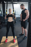 Sportswoman training with trx resistance band while trainer looking at her Royalty Free Stock Photography
