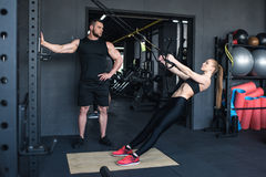 Sportswoman training with trx resistance band while trainer looking at her Royalty Free Stock Photos
