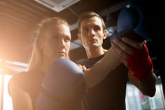 Sportswoman trains boxing with coach Royalty Free Stock Images
