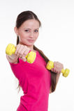 Sportswoman with two dumbbells in the hands of Stock Images