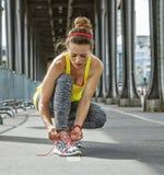 Sportswoman tying shoelaces on Pont de Bir-Hakeim bridge, Paris Royalty Free Stock Photo