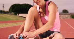 Sportswoman tying up her shoelaces while sitting. On running track stock video footage