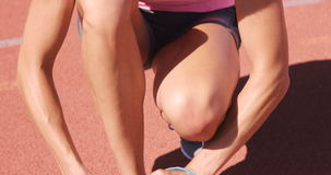 Sportswoman tying up her shoelaces while sitting. On running track stock video