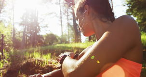 Sportswoman typing in her mobile phone before to run. In a forest stock video footage