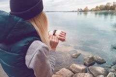 Sportswoman uses an electronic bracelet-pedometer standing on the lake shore. Travel and healthy lifestyle concept. Back. Sportswoman uses an electronic bracelet Stock Photos