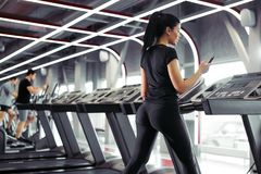 Sportswoman using smartphone for training workout app while jogging on treadmill. Rear view fit Sportswoman using smartphone for training workout app while Stock Photography