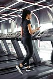 Sportswoman using smartphone for training workout app while jogging on treadmill. Rear view fit Sportswoman using smartphone for training workout app while Stock Image