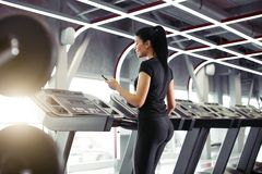 Sportswoman using smartphone for training workout app while jogging on treadmill. Rear view fit Sportswoman using smartphone for training workout app while Royalty Free Stock Photo