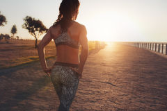 Sportswoman walking on a seaside promenade at sunset Stock Photo