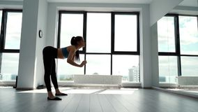 Sportswoman warm up in slow motion in fitness club on background of large window. Attractive brunette doing bends exercise. Woman performs forward and backward stock footage