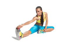 Sportswoman warming up her legs sitting on the floor on white Royalty Free Stock Photo
