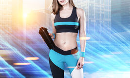 Sportswoman with water bottle in city. Portrait of an unrecognizable sportswoman standing with a water bottle in a sunny city. Toned image Stock Image