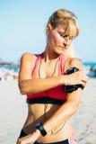 Sportswoman wearing armband on beach Royalty Free Stock Photos