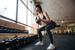 Sportswoman working our and doing squats with kettlebell in gym stock images