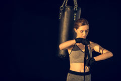 Sportswoman wraping hands with tape with punching bag behind Royalty Free Stock Photos