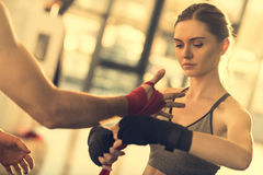 Sportswoman wraping man`s hand with red tape Stock Photos
