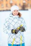 Sportswomanståenden med skidar utrustning Arkivbild
