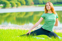 Sportswomen do exercises on the lush grass. In the park Stock Images