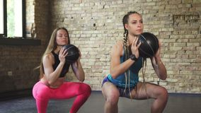 Sportswomen doing squats with medicine balls at the gym. Two yougn athletic women exercising together at the sports studio, doing squats with medicine balls stock video