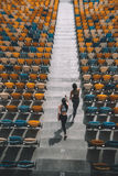 Sportswomen running on stadium stairs, running women concept. Two sportswomen running on stadium stairs, running women concept Royalty Free Stock Photos