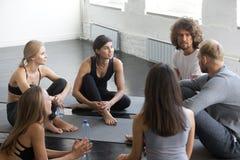Sportteam, das in der Eignungsstudio-Yogalektion spricht lizenzfreie stockbilder