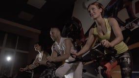 Sporttrio op het fitness centrum die op hometrainer tegelijkertijd uitwerken stock video
