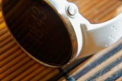 Sportuhr in der weißen Farbe auf Holztisch, intelligente Uhr für Betrieb und Eignungstraining stockbild