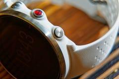 Sportuhr in der weißen Farbe und roter Knopf auf Holztisch, intelligenter Uhr für Betrieb und Eignungstraining lizenzfreies stockfoto