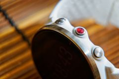 Sportuhr in der weißen Farbe und roter Knopf auf Holztisch, intelligenter Uhr für Betrieb und Eignungstraining stockfotos